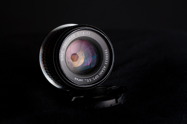 A low key product shot of an old Takumar lens